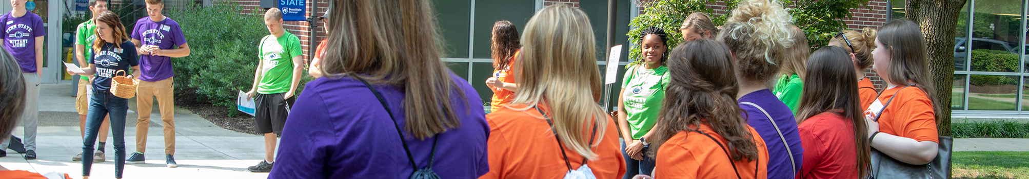 A group of students at orientation learn about Advising outside of the Atrium on a sunny day.