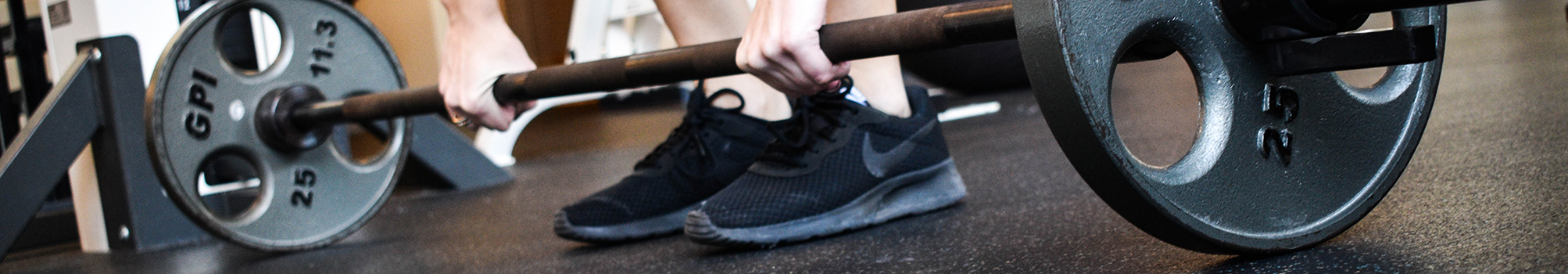 The shoes of a student is shown on the Fitness Center floor between the weights on a dumbbell before it is lifted off the floor.