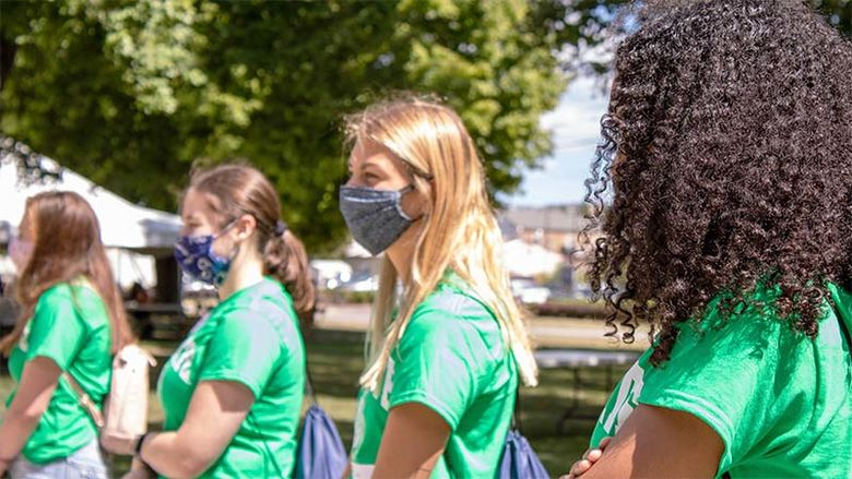 Four female students in masks and green shirts stand side-by-side