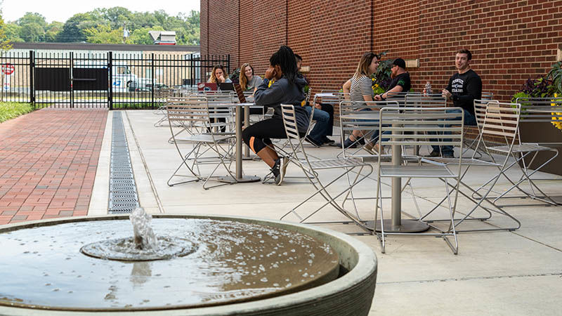 A fountain in the foreground and a courtyard with students sitting in the background