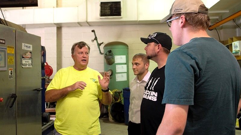 Four men standing together inside local sewer plant