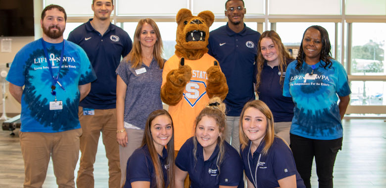 Several men and women pose with the Nittany Lion at LIFE-NWPA