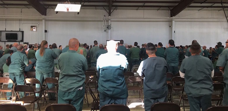 Inmates in Indiana stand in a common room to listen to a speaker.