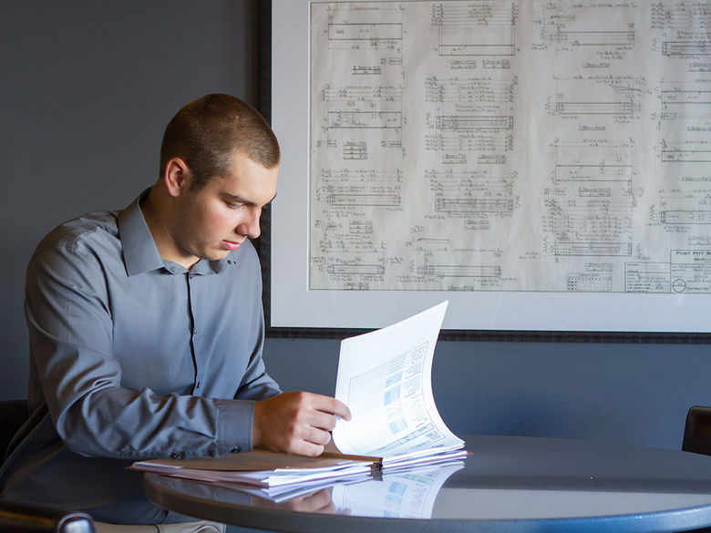 A male student studies papers at his internship at the eCenter