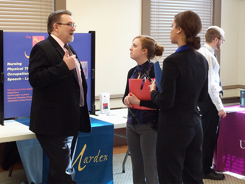 An employer and students talk at a job fair