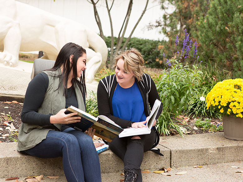 Two female students study in front of the Lion Shrine in the fall.