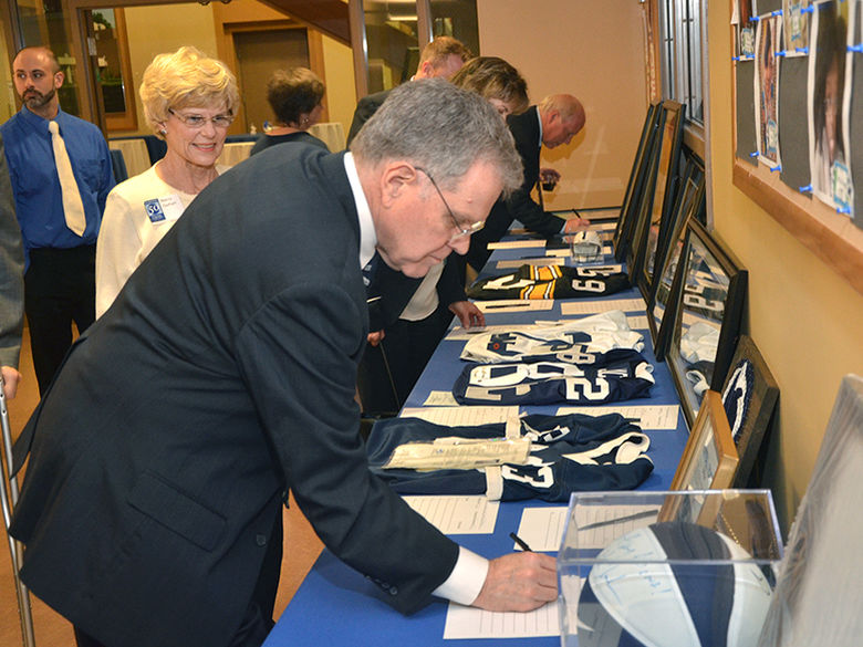 a campus supporter makes a bid on a silent auction item