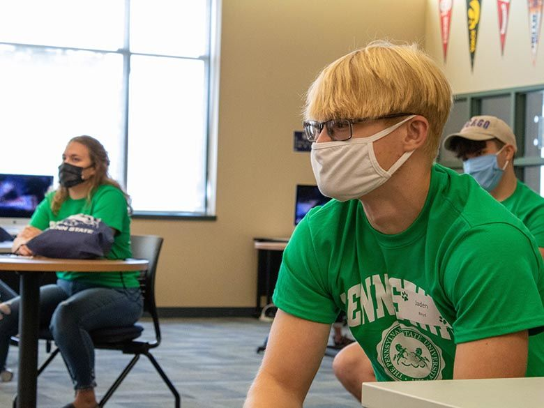 Three students in masks in library