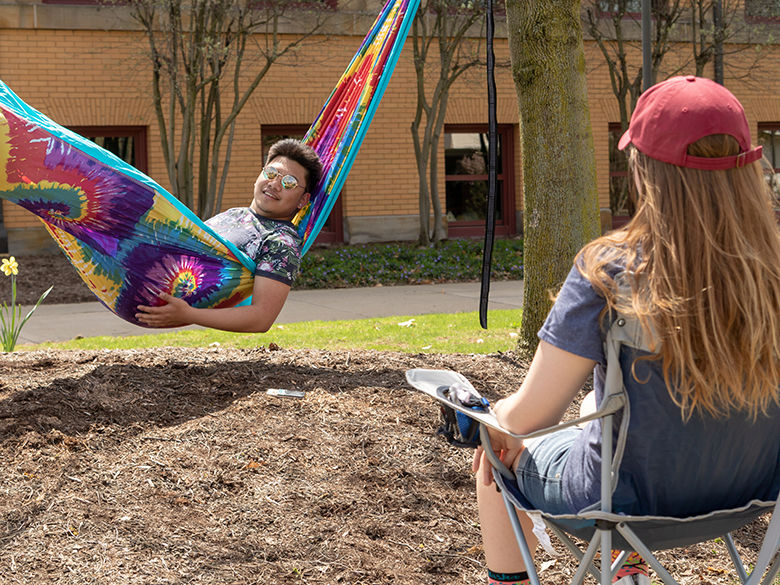 A student lays in a tie-dye print hammock between two trees and talks to a woman with long blonde hair as she sits in a folding chair.