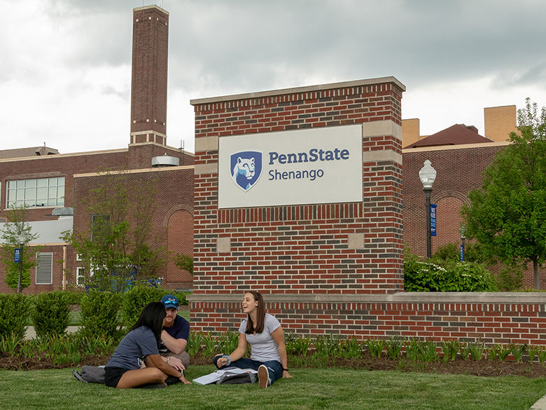 Three students study in front of the campus' from entrance sign
