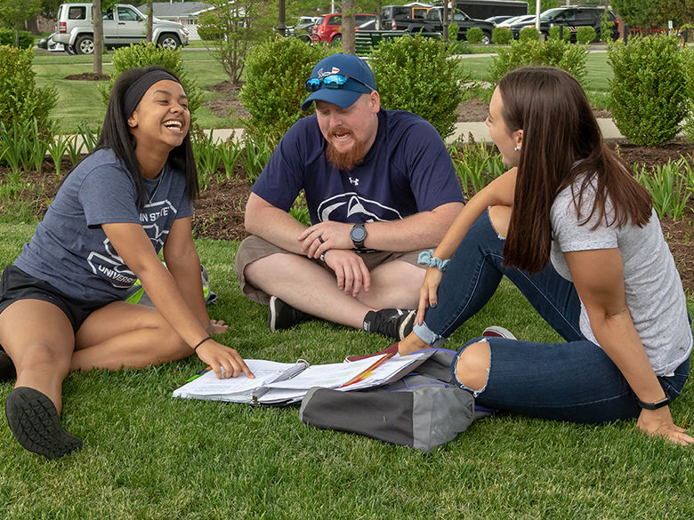 A group of three students study while they sit in the grass on a summer day