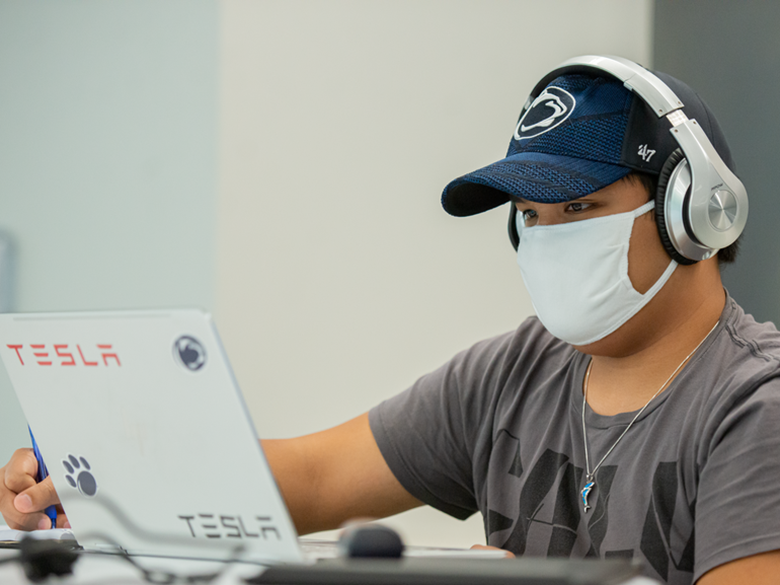 Male student in headphones and a mask working on a laptop