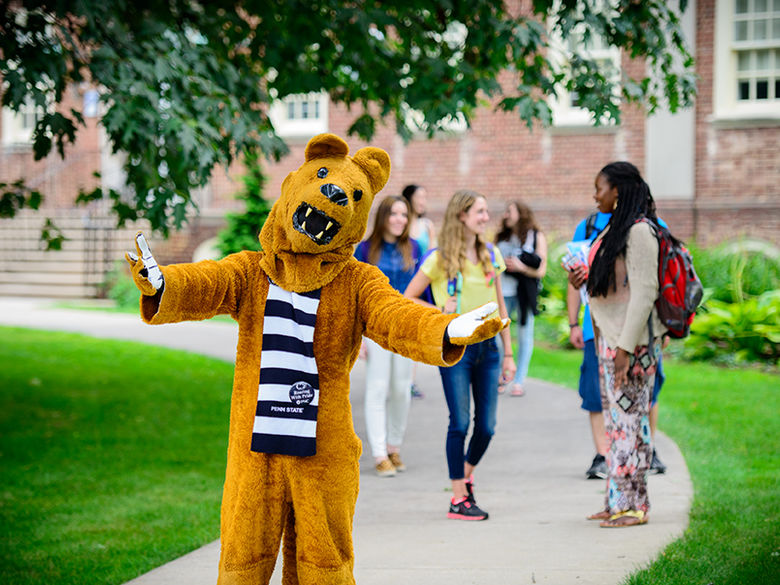 The Nittany Lion stands with arms wide open in front of a group of students