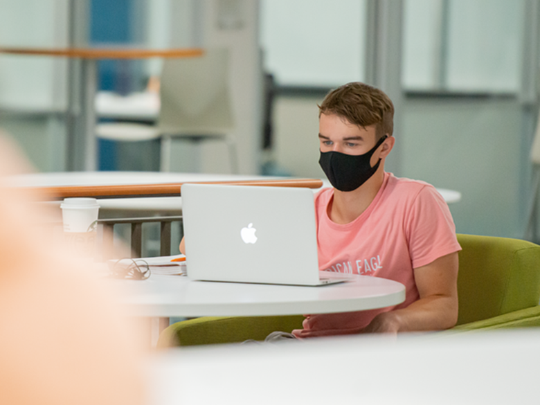 Student in mask in study lounge with laptop