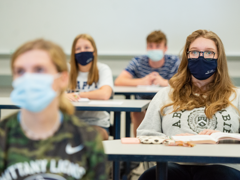 four masked students in a classroom