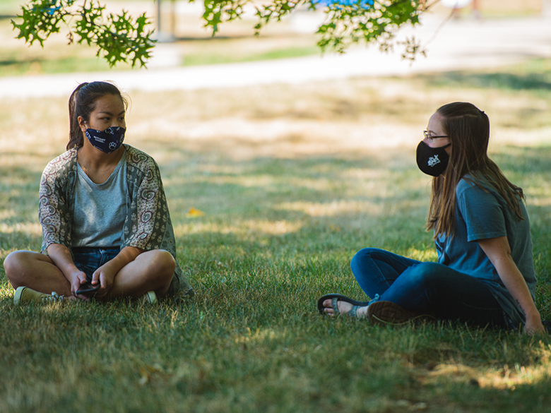 Two female students in masks sitting in grass