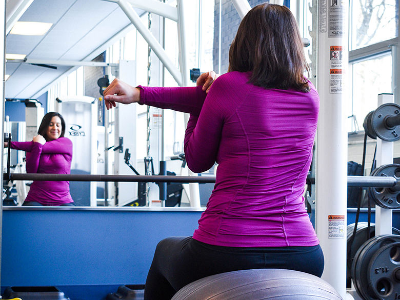 A female student stretches in the Fitness Center