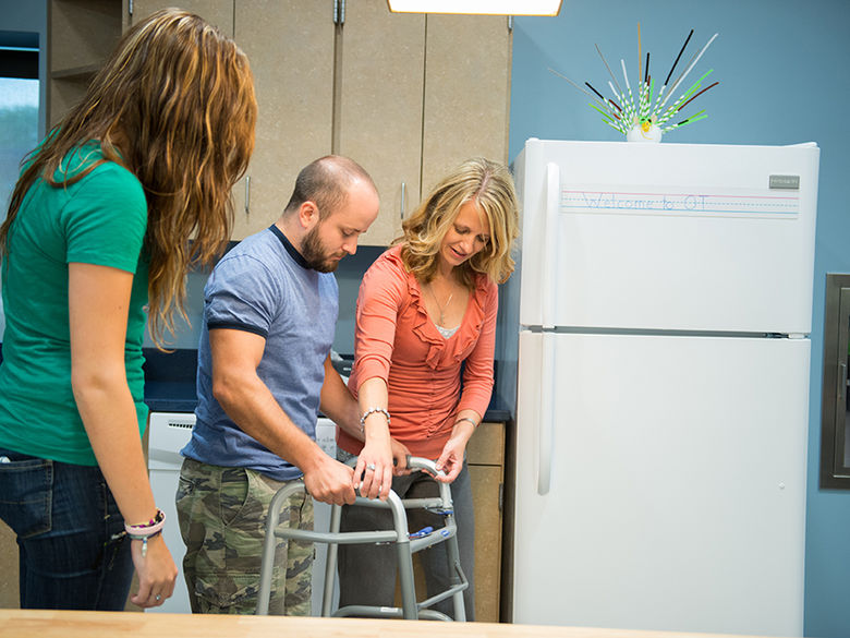 An OTA faculty member teaches a male student how to use a walker while a female student learns from the interaction