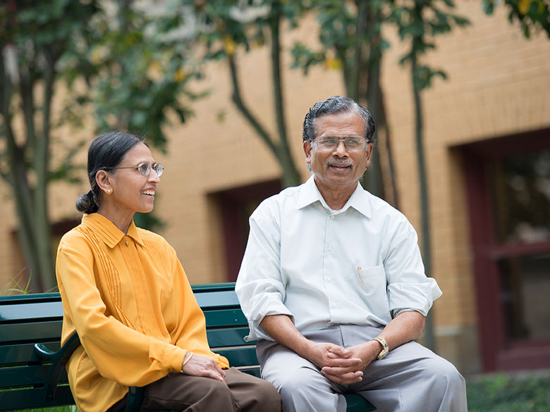 Two faculty members sit on a bench in front of Lecture Hall.