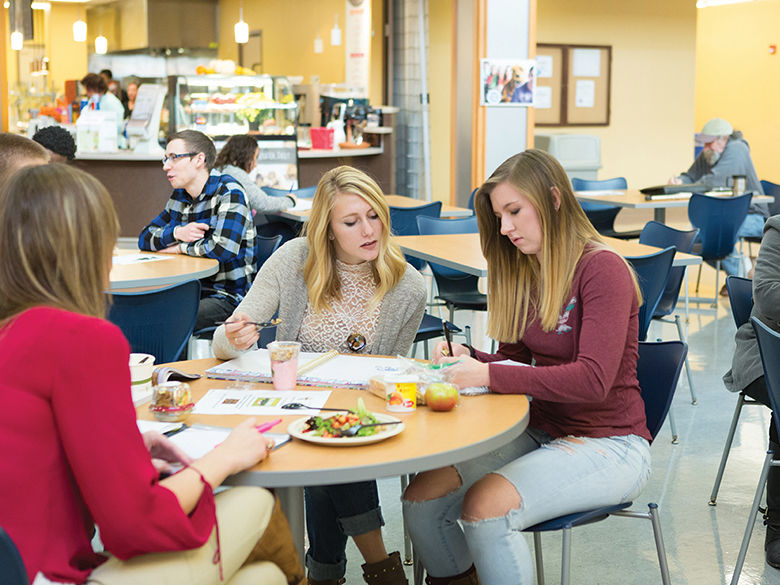 Two female students study and eat in the Lion's Den cafeteria