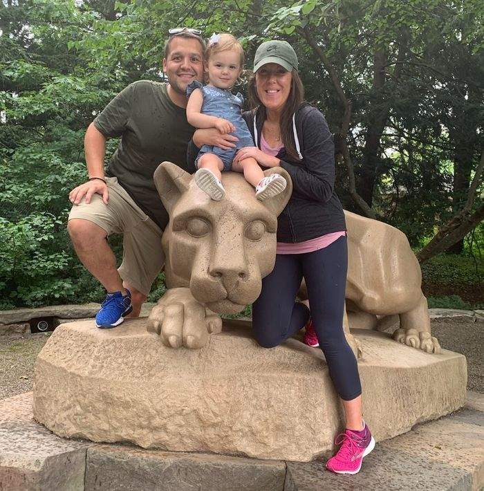 A man, his wife, and young daughter sitting on the Nittany Lion shrine.