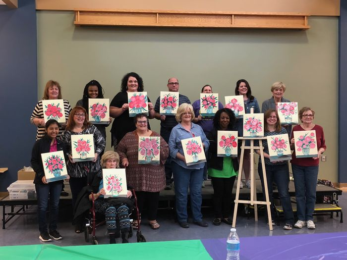 Group of people holding up individual paintings of flowers