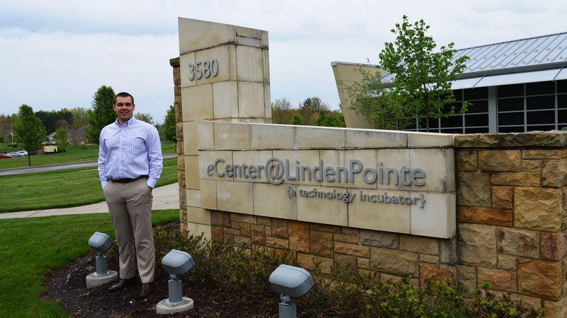 Riley Atterholt in front of the sign at the eCenter@LindenPointe in Hermitage, Pa.