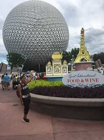 A young woman poses in the front entrance of Epcot in Disney World.