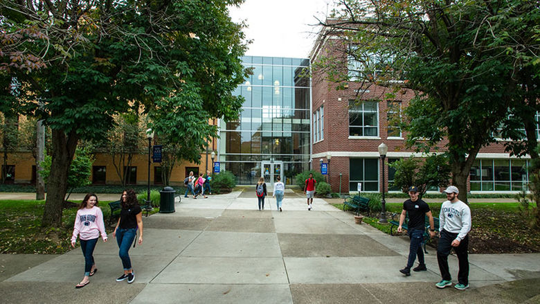 Five groups of students walk on the sidewalks outside of Sharon and Lecture halls on a sunny day.