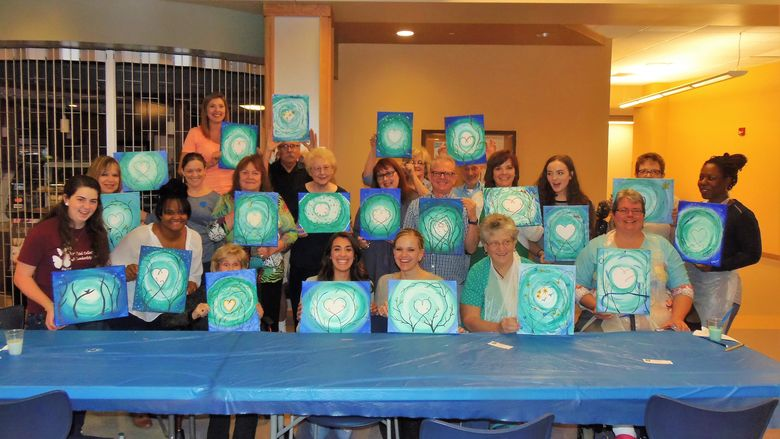 Participants of last year's Scoop & Paint event pose for a picture with their completed projects