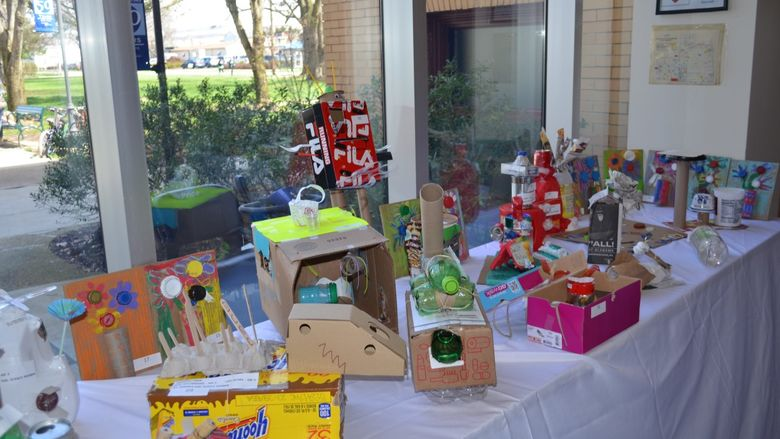 Several upcycled art projects on a table in the campus' Atrium area