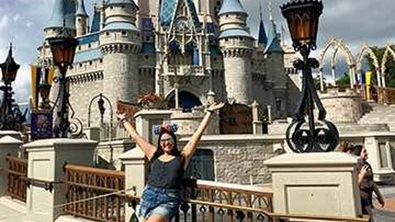 A young woman in front of Disney World's Magic Kingdom.
