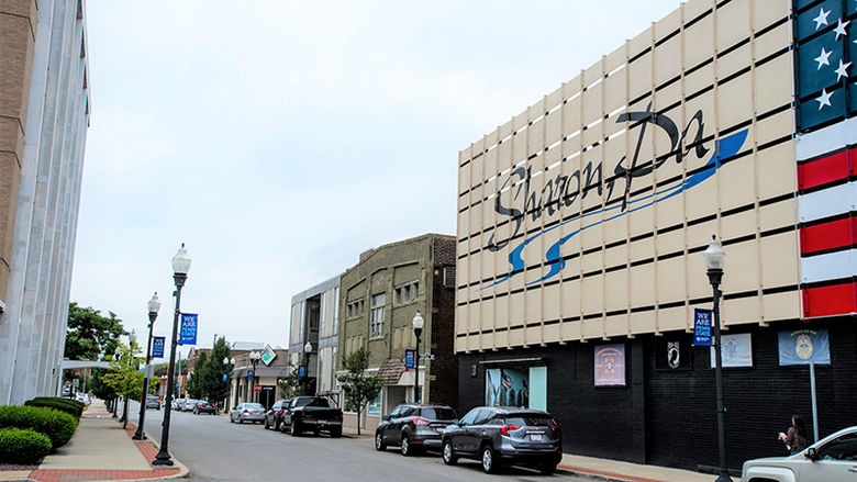 "The Sharon, PA logo is displayed on two stories of a downtown building on Shenango Avenue. The street is lines with cars on one side and, on the other, lamp posts with flags that say ""We are Penn State."""
