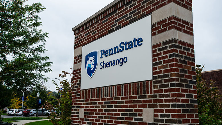 Brick entry sign that features the Penn State Shenango mark. Trees and a parking lot can be seen in the background.