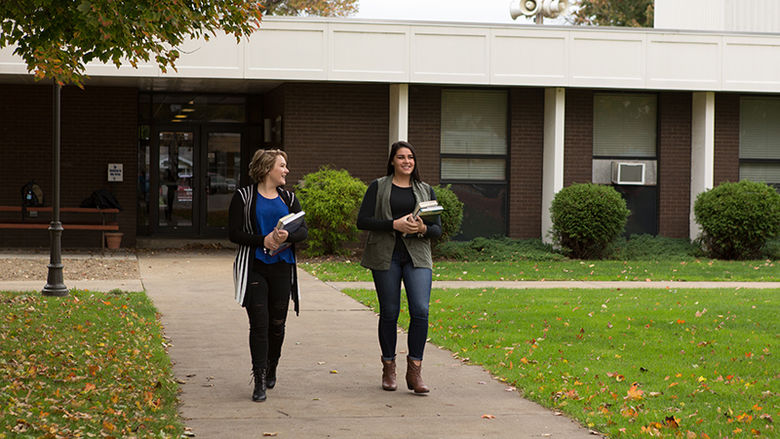 Two female students walk outside of Forker Lab on a fall day with books in hand.