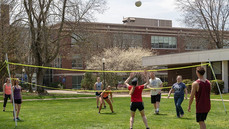 A group of eight Shenango students are hitting the volleyball high into the air and over the net on a sunny day in the grass in front of Forker Lab on campus.