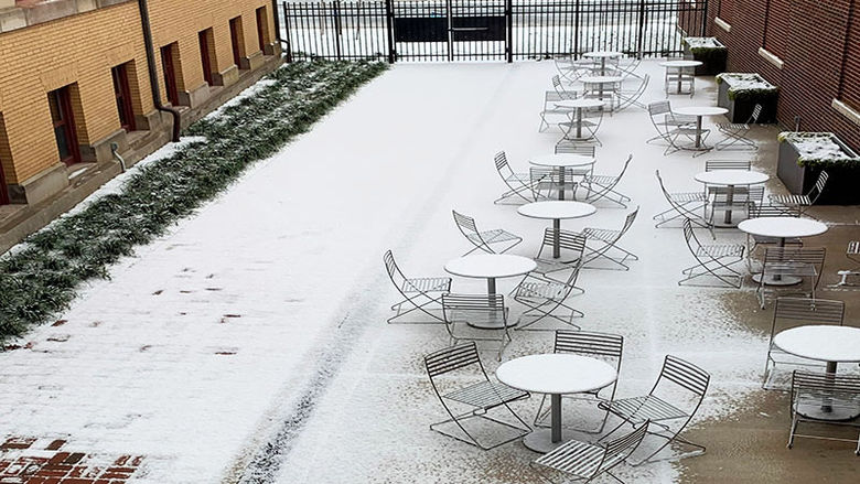 The table and ground of the courtyard are covered in a light dusting of snow. The courtyard is surrounded by Sharon Hall and Lecture Hall on either side.