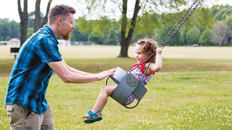 Nick Taylor pushes a preschooler on a swing