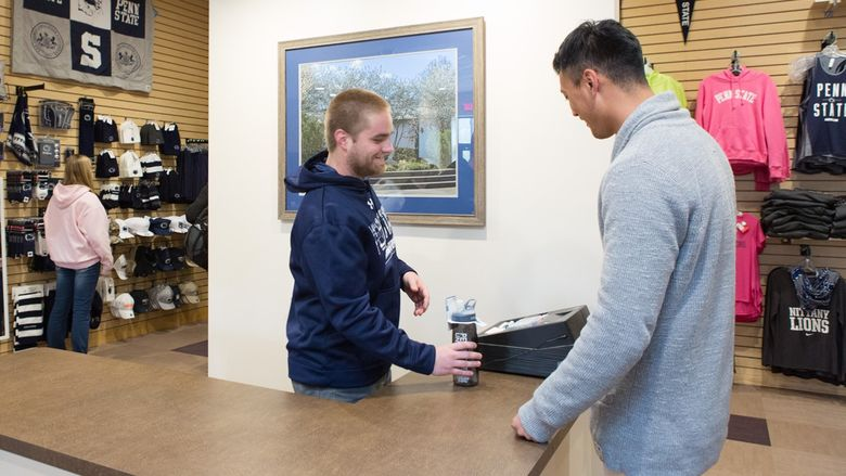 A student intern waits on a customer inside of The Nittany Connection in downtown Sharon.
