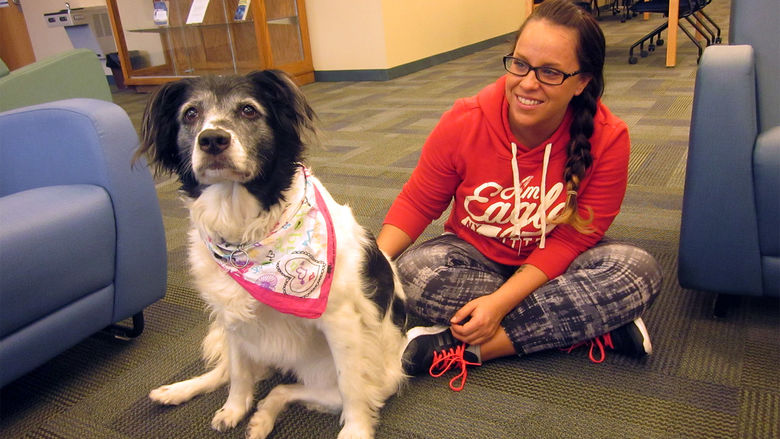 a therapy dog sits with student Dani Johnson in the library