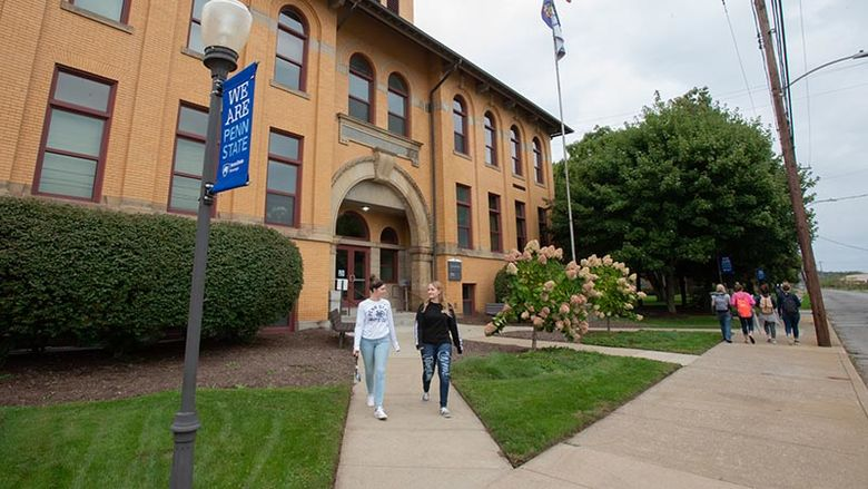 Two students walk out of Lecture Hall on a sidewalk while four other students walk along Shenango Avenue.