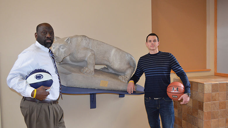 Two Penn State staff members standing with basketballs next to the Nittany Lion located in the campus' atrium area