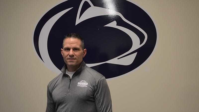 Man stands in front of the Nittany Lion Athletic mark