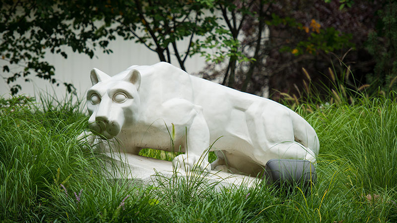 Lion statue surrounded by tall grass